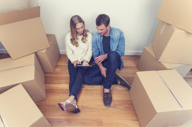 Young couple sitting in new house with packing boxes.
